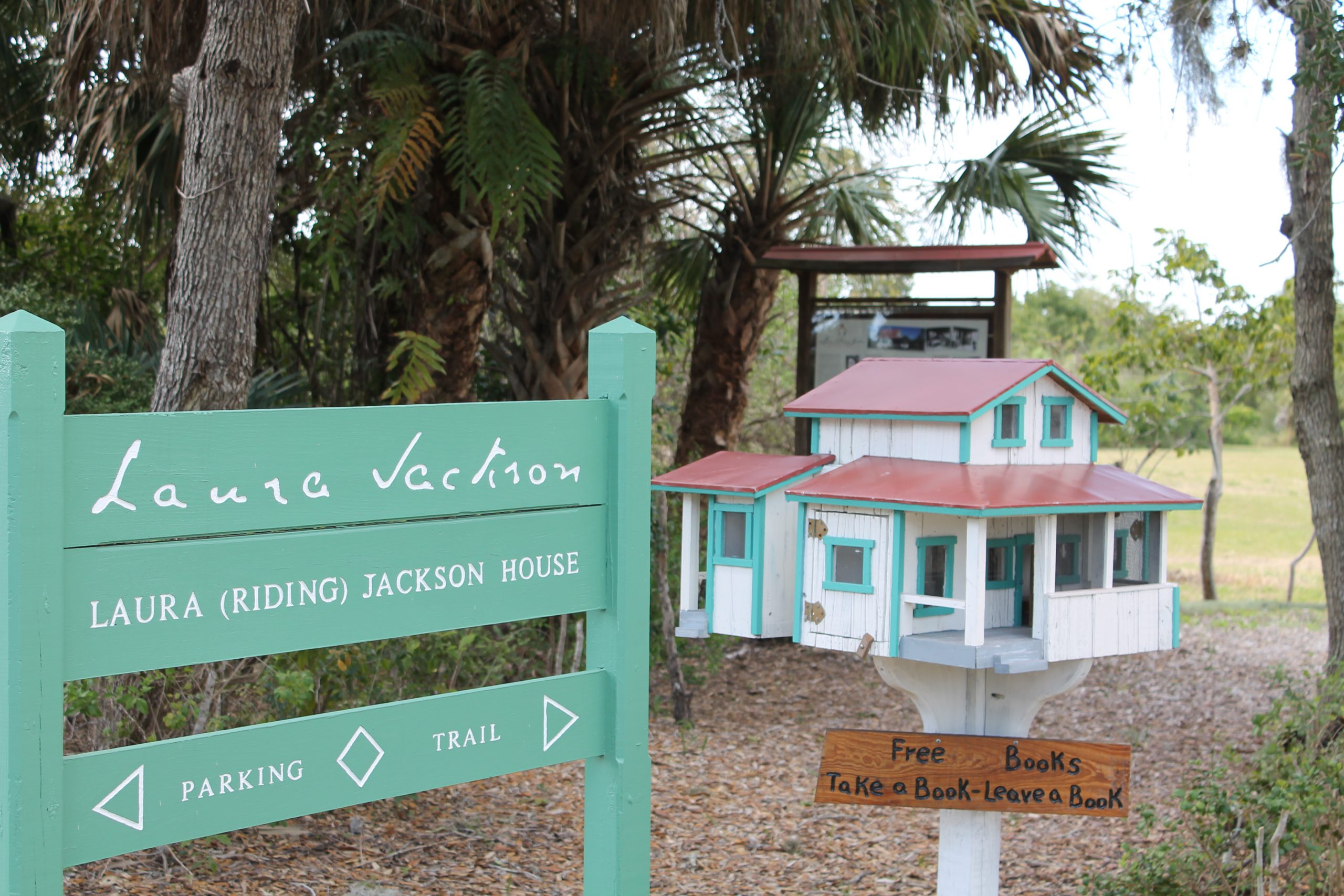 Laura (Riding) Jackson small wooden house and teal sign